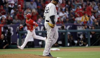 New York Yankees starting pitcher CC Sabathia, center right, walks off the mound after giving up a solo home run to Los Angeles Angels' Andrelton Simmons, background left, during the first inning of a baseball game Wednesday, April 24, 2019, in Anaheim, Calif. (AP Photo/Marcio Jose Sanchez)