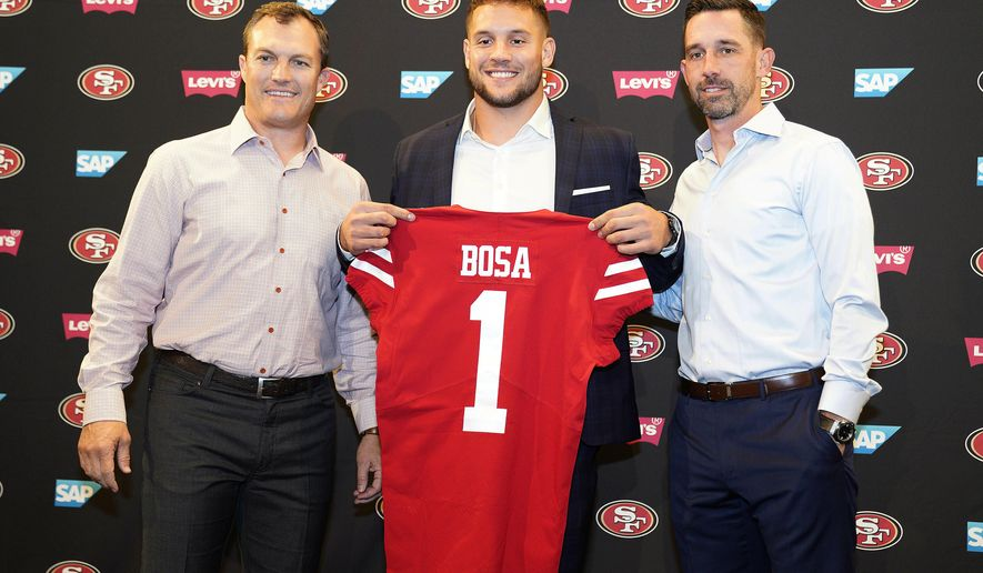 San Francisco 49ers first-round pick Nick Bosa, center, holds up a jersey next to general manager John Lynch, left, and coach Kyle Shanahan, right, during an NFL football news conference, Friday, April 26, 2019, in Santa Clara, Calif. (AP Photo/Tony Avelar )