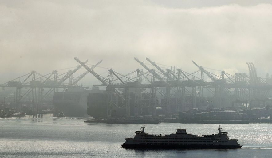 In this Dec. 31, 2018, photo a Washington state ferry sails on a foggy day near cranes at the Port of Seattle. On Friday, April 26, 2019, the Commerce Department issues the first estimate of how the U.S. economy performed in the January-March quarter. (AP Photo/Ted S. Warren, File)