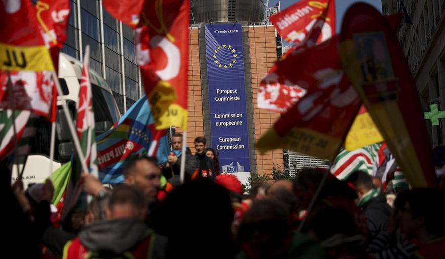 People listen to speeches near the European Commission headquarters, background, during a protest by European trade unions in Brussels, Friday, April 26, 2019. Thousands of trade union demonstrators protested outside of European Union headquarters to demand better protection and working conditions in the wake of next month's EU-wide elections. (AP Photo/Francisco Seco)