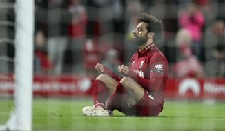 Liverpool's Mohamed Salah sits in front of the goal after scoring his side's fifth goal during the English Premier League soccer match between Liverpool and Huddersfield Town at Anfield Stadium, in Liverpool, England, Friday, April 26, 2019.(AP Photo/Jon Super)