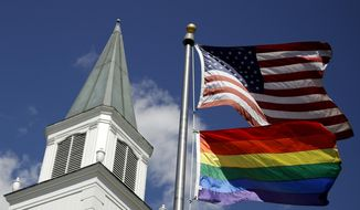FILE - In this April 19, 2019 file photo, a gay pride rainbow flag flies along with the U.S. flag in front of the Asbury United Methodist Church in Prairie Village, Kan. On Friday, April 26, 2019, the United Methodist Church's judicial council upheld the legality of major portions of a new plan that strengthens the denomination's bans on same-sex marriage and ordination of LGBT pastors. (AP Photo/Charlie Riedel)