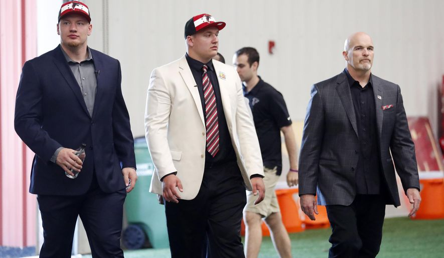 Atlanta Falcons head football coach Dan Quinn, right, arrives for a media session with NFL football first-round-draft picks Kaleb McGary, left, from Washington, and Chris Lindstrom, of Boston College, Friday, April 26, 2019, in Flowery Branch, Ga. Lindstrom and McGary are both offensive linemen. (AP Photo/John Bazemore)