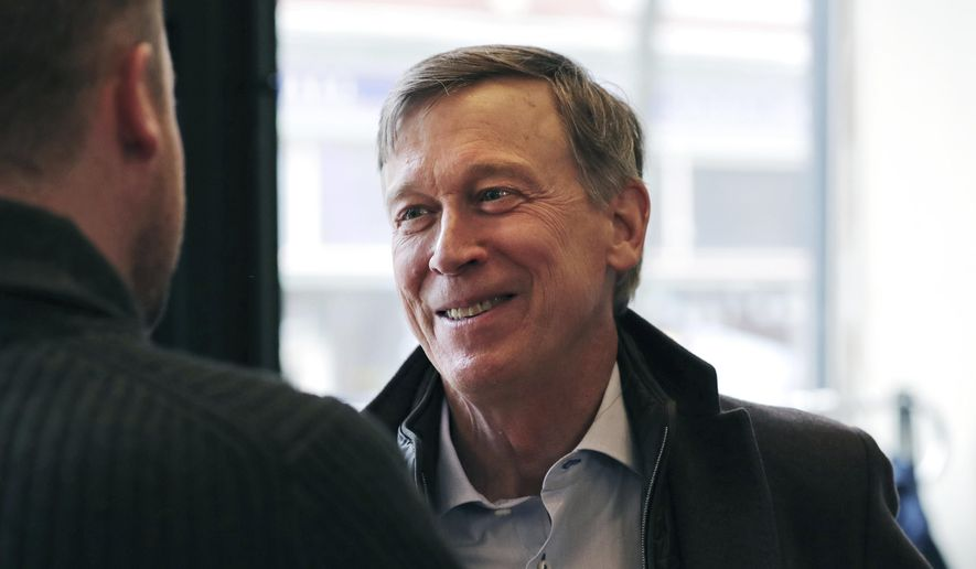 In this March 22, 2019, file photo, former Democratic Colorado Gov. John Hickenlooper talks with AmeriCorps members prior to a roundtable campaign stop in Manchester, N.H. (AP Photo/Charles Krupa, File)