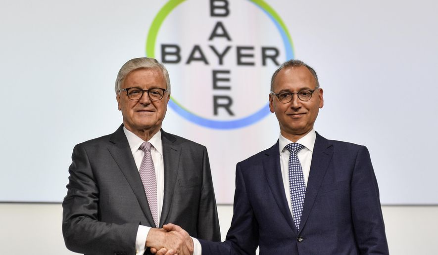 CEO Werner Baumann, right, and Chairman of the Supervisory Board Werner Wenning, left, shake hands during the annual general meeting of the Bayer stock company in Bonn, Germany, Friday, April 26, 2019. Following the record acquisition of U.S. biotech and seed company Monsanto, Bayer's agricultural business has become a risk for the German chemical company. Bayer is facing enormous cost if the U.S. court will find Monsanto's glyphosate to be causing cancer. Since the take-over of Monsanto in June 2018, Bayer lost around half of its value in market capitalization. (AP Photo/Martin Meissner)