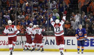 Carolina Hurricanes players celebrate after Jordan Staal, second from left, scored a goal on the New York Islanders during overtime of Game 1 of an NHL hockey second-round playoff series, Friday, April 26, 2019, in New York. The Hurricanes won 1-0. (AP Photo/Julio Cortez)