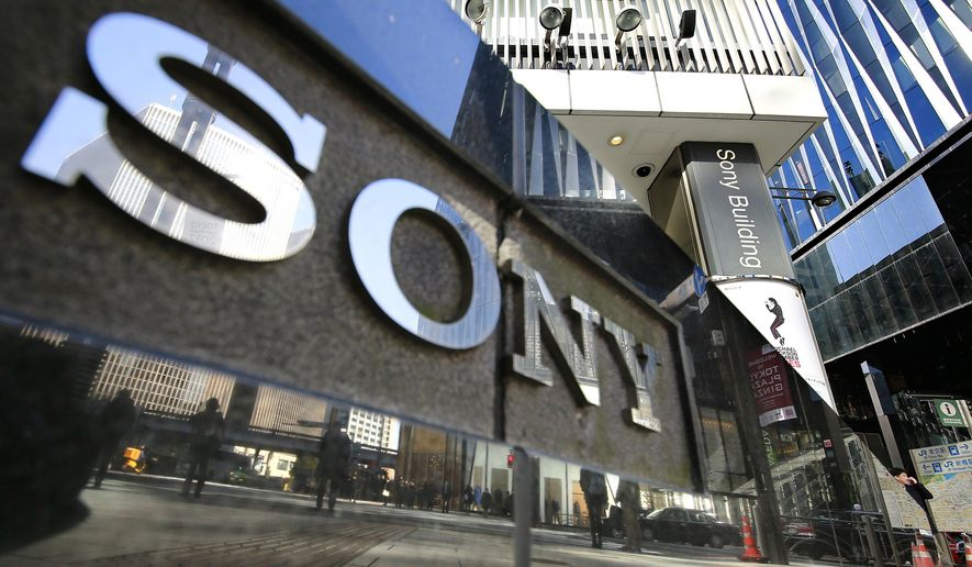 FILE - In this Feb. 2, 2017, file photo, people are reflected on a wall of the Sony showroom building at Ginza shopping district in Tokyo.  Sony has reverted to profitability for the quarter through March, boosted by robust demand for game software and network services, as well as gains from Spotify, according to its report released by Friday, April 26, 2019. (AP Photo/Shizuo Kambayashi, File)