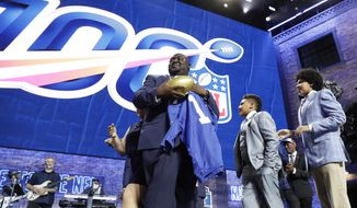 New York Giants fan Greg Hampton, holds a jersey after winning two season tickets for the team for the next century, during in the first round at the NFL football draft, Thursday, April 25, 2019, in Nashville, Tenn. As part of the NFL's celebration of its 100th season, which begins in September, the league held a contest that drew about 5,000 entrants. (AP Photo/Mark Humphrey)