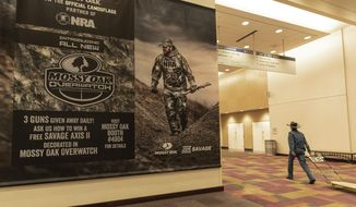 A poster hangs on the wall of the Indianapolis Convention Center on Thursday, April 25, 2019, where members of the National Rifle Association will be holding its 148th annual meetings in Indianapolis. The group's meetings come at a tumultuous time within the gun-rights organization. (AP Photo/Lisa Marie Pane)