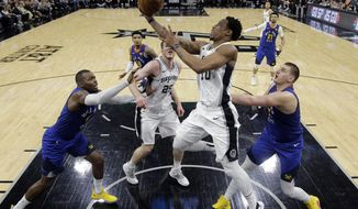 San Antonio Spurs guard DeMar DeRozan (10) drives to the basket against Denver Nuggets forward Paul Millsap (4) and center Nikola Jokic (15) during the second half of Game 6 of an NBA basketball playoff series, Thursday, April 25, 2019, in San Antonio. San Antonio won 120-103. (AP Photo/Eric Gay)