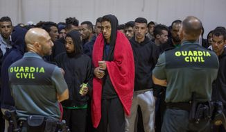 FILE - In this June 28, 2018 photo, Guardia Civil officers stand guard as migrants stay at a makeshift emergency center for migrants at Barbate's municipal sports center, in the south of Spain, after being rescued by Spain's Maritime Rescue Service in the Strait of Gibraltar. Spain appears to have stemmed a surge in illegal migration that made it the main Mediterranean entry point for migrants seeking ways into Europe by increasing Morocco's involvement in border control. (AP Photo/Emilio Morenatti, File)
