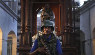 A Sri Lankan soldier stands guard at the damaged St. Anthony's Church or Shrine in Colombo, Sri Lanka, Friday, April 26, 2019. Priests have allowed journalists inside St. Anthony's Church in Sri Lanka for the first time since it was targeted in a series of Islamic State-claimed suicide bombings that killed over 250 people. Broken glass littered the sanctuary's damaged pews and blood stained the floor. Shoes left by panicked worshippers remained in the darkened church, and broken bottles of holy water lay on the floor. (AP Photo/Manish Swarup)