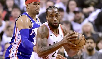 Philadelphia 76ers forward Tobias Harris, left, watches as Toronto Raptors forward Kawhi Leonard (2) moves the ball during the first half of Game 1 of a second-round NBA basketball playoff series in Toronto, Saturday, April 27, 2019. (Frank Gunn/The Canadian Press via AP)