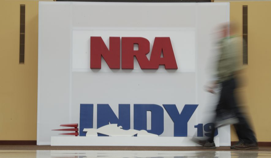 A visitor to the at the National Rifle Association Annual Meeting walks past signage for the event in Indianapolis, Saturday, April 27, 2019. (AP Photo/Michael Conroy) ** FILE **