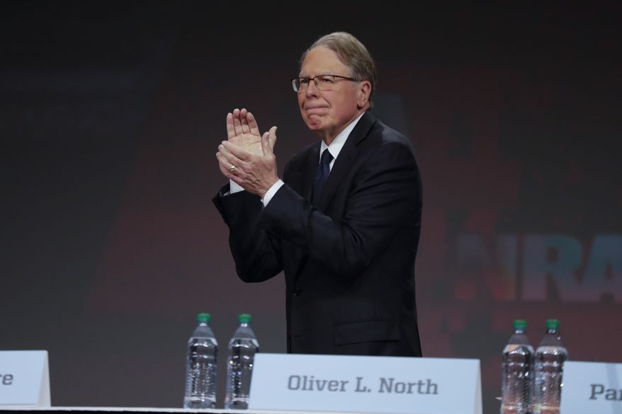 Nation Rifle Association Executive Vice President Wayne LaPierre applauds behind the empty seat of Retired Lt. Col. Oliver North at the NRA Annual Meeting of Members in Indianapolis, Saturday, April 27, 2019. North has announced that he will not serve a second term as president of the NRA amid inner turmoil in the gun-rights group. (AP Photo/Michael Conroy)