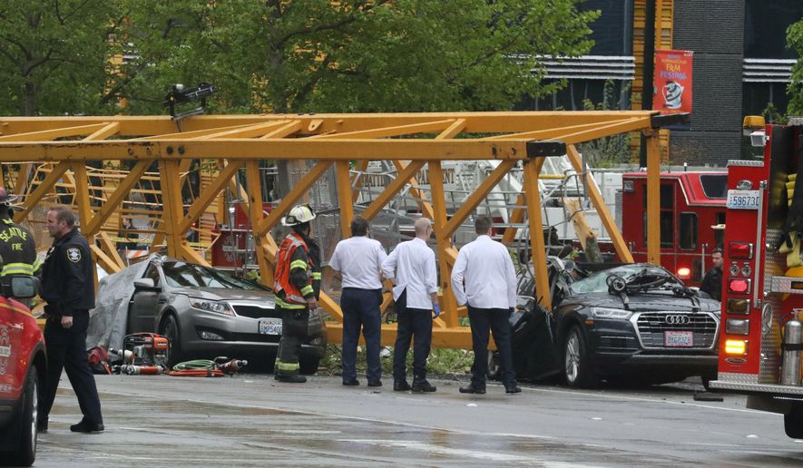 Emergency crews work at the scene of a construction crane collapse near the intersection of Mercer Street and Fairview Avenue near Interstate 5 Saturday, April 27, 2019, in Seattle. Several people were killed and others wounded when the crane collapsed Saturday afternoon in downtown Seattle, pinning cars underneath. (Alan Berner/The Seattle Times via AP)