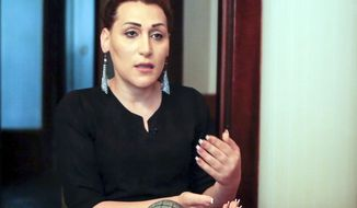 In this frame grab taken from the Associated Press Television footage on Friday, April 26, 2019, Lilit Martirosian, a founder of the Armenian transgender organization Right Side, gestures while her interview for the Associated Press in Yerevan, Armenia. A transgender woman whose address to the Armenian parliament caused an uproar says she has received death threats and is avoiding leaving her home because of security concerns. (AP Photo/Sona Kocharyan)