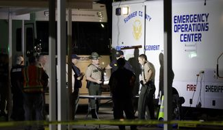 Law enforcement officials work at a command center set up at North Sumner Elementary School Saturday, April 27, 2019, in Bethpage, Tenn. Authorities said they found several bodies in two homes Saturday, prompting a massive manhunt for a possibly armed suspect. (AP Photo/Mark Humphrey)