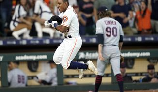 Houston Astros' Tony Kemp, left, celebrates after hitting the game-winning home run as Cleveland Indians relief pitcher Adam Cimber (90) walks to the dugout during the 10th inning of a baseball game Saturday, April 27, 2019, in Houston. The Astros won 4-3. (AP Photo/David J. Phillip)