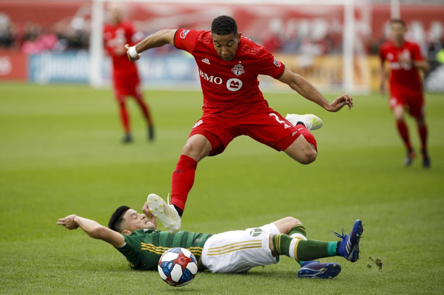 Toronto FC defender Justin Morrow, top, leaps over Portland Timbers defender Jorge Moreira, bottom, during first-half MLS soccer match action at BMO field in Toronto, Saturday, April 27, 2019. (Cole Burston/The Canadian Press via AP)