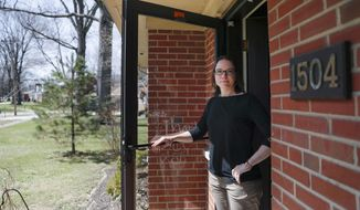 Mindy Nagel poses for a photograph at the threshold of her home, Monday, April 1, 2019, in Cincinnati. Mindy usually votes Democratic; while husband Tom usually goes Republican. But that's only part of it: their bedroom is in Ohio's 1st Congressional District while their garage is in the 2nd. (AP Photo/John Minchillo)