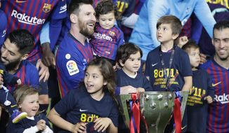 Barcelona forward Lionel Messi with his children pose with the trophy after winning the Spanish League title, at the end of the Spanish La Liga soccer match between FC Barcelona and Levante at the Camp Nou stadium in Barcelona, Spain, Saturday, April 27, 2019. Barcelona clinched the Spanish La Liga title, with three matches to spare, after it defeated Levante 1-0. (AP Photo/Manu Fernandez)