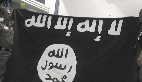 """In this Friday, April 26, 2019, image made from video, officers hold up an Islamic State group flag in Arabic that reads: """"There is no God, but Allah"""" and """"Allah, Prophet, Muhammad"""" during a raid on a house in Sainthamaruthu, Sri Lanka. Militants linked to Easter suicide bombings opened fire and set off explosives during a raid by Sri Lankan security forces on the house in the country's east, leaving behind a grisly discovery Saturday: 15 bodies, including six children. (AP Photo)"""