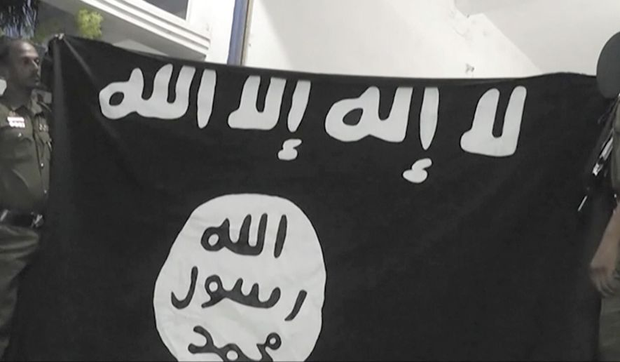 "In this Friday, April 26, 2019, image made from video, officers hold up an Islamic State group flag in Arabic that reads: ""There is no God, but Allah"" and ""Allah, Prophet, Muhammad"" during a raid on a house in Sainthamaruthu, Sri Lanka. Militants linked to Easter suicide bombings opened fire and set off explosives during a raid by Sri Lankan security forces on the house in the country's east, leaving behind a grisly discovery Saturday: 15 bodies, including six children. (AP Photo)"