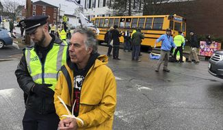 A protester is arrested outside Bath Iron Works prior to the christening ceremony for a Zumwalt-class guided missile destroyer named for former President Lyndon Baines Johnson, Saturday, April 27, 2019, in Bath, Maine. (AP Photo/David Sharp)