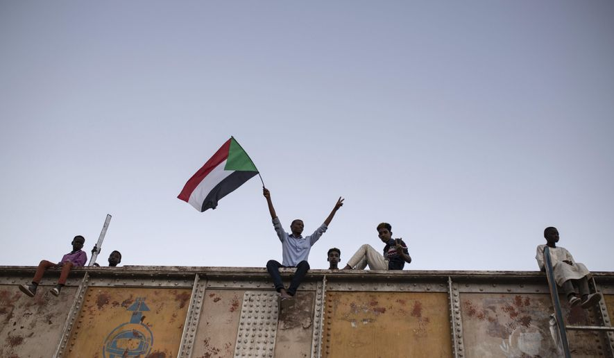 A protester waves a Sudanese national flag during a sit-in at Armed Forces Square in Khartoum, Sudan, Saturday, April 27, 2019. The Umma party of former Prime Minister Sadiq al-Mahdi, a leading opposition figure, said the protesters will not leave until there is a full transfer of power to civilians. (AP Photos/Salih Basheer)