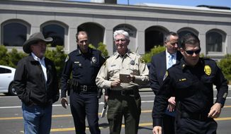 San Diego County Sheriff Bill Gore, center, arrives with other law enforcement officials outside of the Chabad of Poway Synagogue Saturday, April 27, 2019, in Poway, Calif. Several people were injured in a shooting at the synagogue. (AP Photo/Denis Poroy)