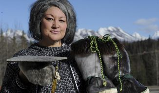 Jacqueline D. Morris displays the seal skin cap and mukluks that her son Tigran Andrew wore during the 2018 Service High School commencement in Anchorage, Alaska, Monday, April 15, 2019. Starting this year, Anchorage graduates can wear traditional tribal regalia and objects of cultural significance at their graduation ceremonies. School district administrators approved the new regulation last month. (Bill Roth/Anchorage Daily News via AP)
