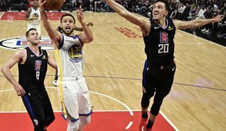 Golden State Warriors guard Stephen Curry, center, shoots as Los Angeles Clippers forward Danilo Gallinari, left, and guard Landry Shamet defend during the second half in Game 6 of a first-round NBA basketball playoff series Friday, April 26, 2019, in Los Angeles. The Warriors won 129-110. (AP Photo/Mark J. Terrill)