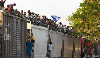 Central American migrants ride atop a freight train during their journey toward the U.S.-Mexico border; in Ixtepec, Mexico, on Tuesday. (Associated Press)