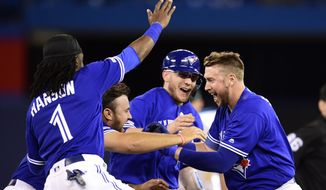 Toronto Blue Jays first baseman Justin Smoak, right, is mobbed by teammates after driving in the winning run against the Oakland Athletics during 11th-inning baseball game action in Toronto, Sunday, April 28, 2019. (Frank Gunn/The Canadian Press via AP)