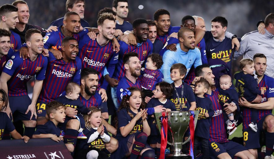 FC Barcelona players, with their children, pose with their trophy after winning the Spanish League title, at the end of the Spanish La Liga soccer match between FC Barcelona and Levante at the Camp Nou stadium in Barcelona, Spain, Saturday, April 27, 2019. Barcelona clinched the Spanish La Liga title, with three matches to spare, after it defeated Levante 1-0. (AP Photo/Manu Fernandez)