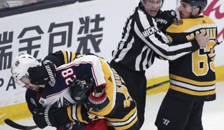 Columbus Blue Jackets right wing Oliver Bjorkstrand (28) and Boston Bruins defenseman Torey Krug tangle as linesman Mark Shewchyk holds back Bruins left wing Brad Marchand at the end of the first period of Game 2 of an NHL hockey second-round playoff series, Saturday, April 27, 2019, in Boston. (AP Photo/Charles Krupa)