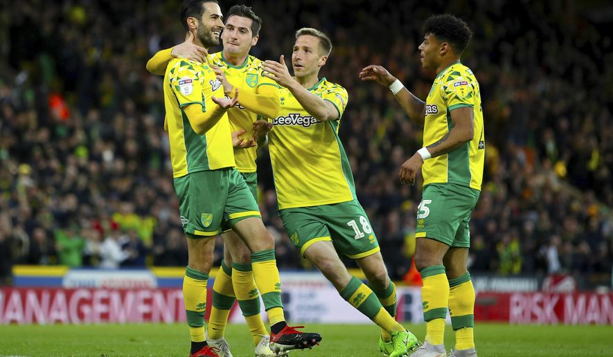 Norwich City's Mario Vrancic, left, celebrates scoring his side's second goal of the game during the English Championship soccer match at Carrow Road, Norwich, England, Saturday April 27, 2019. Norwich is returning to the Premier League after a three-year absence _ and Sheffield United is likely to be promoted, too.Norwich, a club from eastern England, clinched one of the two automatic promotion places from the second-tier League Championship by beating Blackburn 2-1 on Saturday.(Chris Radburn/PA via AP)