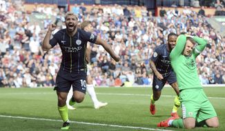 Manchester City's Sergio Aguero, left, celebrates after scoring his side's opening goal during the English Premier League soccer match between Burnley and Manchester City at Turf Moor in Burnley, England, Sunday, April 28, 2019. (AP Photo/Rui Vieira)