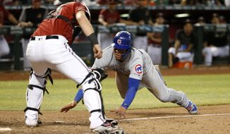 Chicago Cubs' Willson Contreras, right, attempts to steal home as Arizona Diamondbacks catcher Carson Kelly waits to make the tag during the 13th inning of a baseball game, Sunday, April 28, 2019, in Phoenix. Contreras was out on the play. (AP Photo/Ralph Freso)