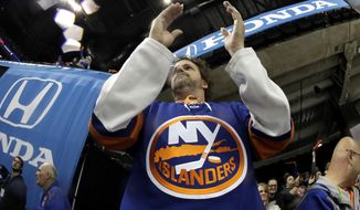 A spectator reacts during the first period of Game 1 of an NHL hockey second-round playoff series between the New York Islanders and the Carolina Hurricanes, Friday, April 26, 2019, in New York. (AP Photo/Julio Cortez)