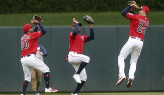 Minnesota Twins outfielders, from left, Eddie Rosario, Byron Buxton and Max Kepler celebrate with basketball-like shooting moves in the Twins 4-1 win over the Baltimore Orioles after a baseball game Sunday, April 28, 2019, in Minneapolis. The Twins won 4-1. Kepler and Buxton both hit home runs. (AP Photo/Jim Mone)