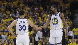 Golden State Warriors guard Stephen Curry (30) reacts with forward Kevin Durant (35) during the first half of Game 1 of a second-round NBA basketball playoff series against the Houston Rockets in Oakland, Calif., Sunday, April 28, 2019. (AP Photo/Jeff Chiu)