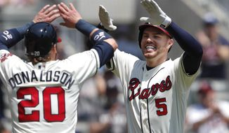 Atlanta Braves first baseman Freddie Freeman (5), right, celebrates with Josh Donaldson (20) after hitting a two-run home run in the first inning of a baseball game against the Colorado Rockies Sunday, April 28, 2019, in Atlanta. (AP Photo/John Bazemore)
