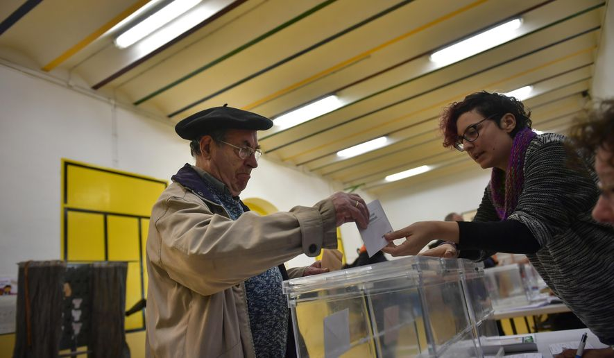 A man casts his vote at a polling station for the general election in Pamplona, Spain, Sunday, April 28, 2019. A divided Spain is voting in its third general election in four years, with all eyes on whether the rise of conservative nationalism will allow the right wing to unseat the incumbent prime minister. (AP Photo/Alvaro Barrientos)