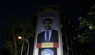 An poster featuring Popular Party leader Pablo Casado looks down from a building on election day in Madrid, Sunday, April 28, 2019. A divided Spain voted Sunday in its third general election in four years, with all eyes on whether a far-right party will enter Parliament for the first time in decades and potentially help unseat the Socialist government. (AP Photo/Andrea Comas)