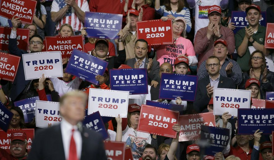 President Donald Trump speaks at a Make America Great Again rally as supporters hold up sign Saturday, April 27, 2019, in Green Bay, Wis. (AP Photo/Mike Roemer)