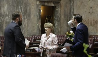 Democratic Sen. Marko Liias, left, Republican Sen. Shelly Short, center, and Democratic Majority Leader Andy Billig talk on the Senate floor on Sunday, April 28, 2019, in Olympia, Wash. State lawmakers are wrapping up a 105-day legislative session in which they were tasked with passing a new, two-year state budget. (AP Photo/Rachel La Corte)