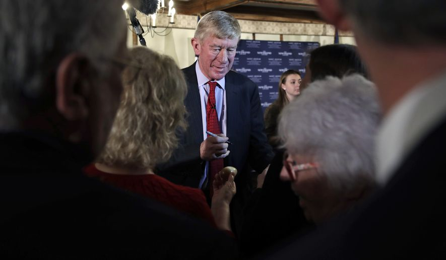 Former Massachusetts Gov. William Weld signs autographs during a New England Council 'Politics & Eggs' breakfast in Bedford, N.H., Friday, Feb. 15, 2019. Weld announced he's creating a presidential exploratory committee for a run in the 2020 election. (AP Photo/Charles Krupa)