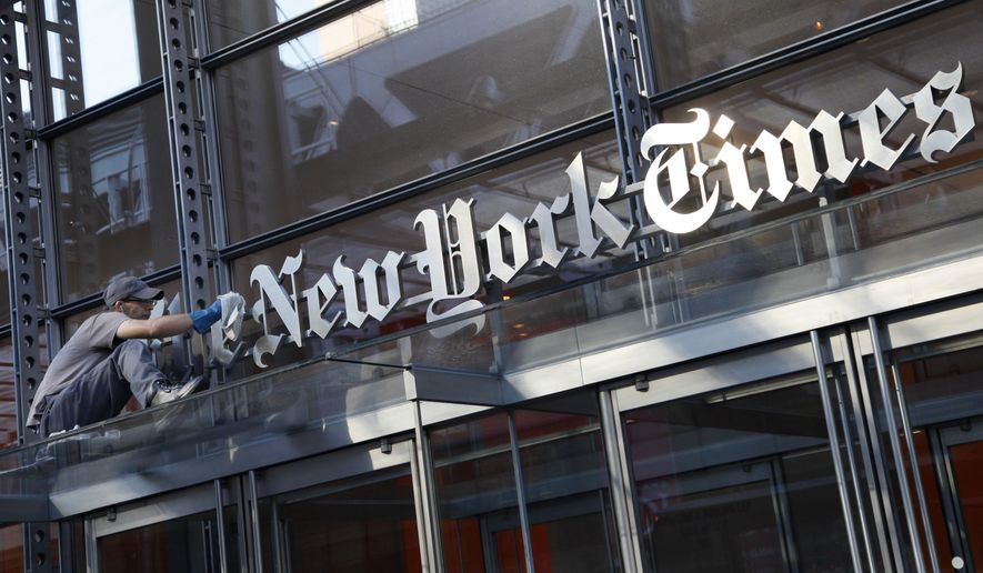 A man polishes the sign for The New York Times at the company's headquarters, July 18, 2013, in New York. (AP Photo/Mark Lennihan) ** FILE **